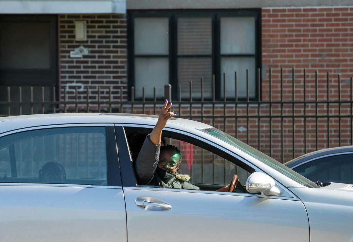 """A woman exclaims """"Justice for George Floyd"""" while driving past Cuney Homes, following the guilty verdict on all counts in the murder trial of former Minneapolis Officer Derek Chauvin, on Tuesday, April 20, 2021, in Third Ward, Houston."""