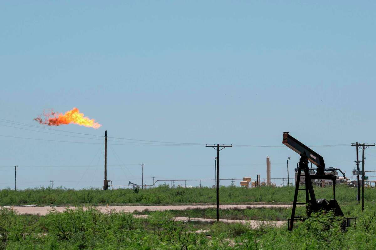 A flare stack is pictured next to pump jacks and other oil and gas infrastructure on April 24, 2020 near Odessa, Texas.