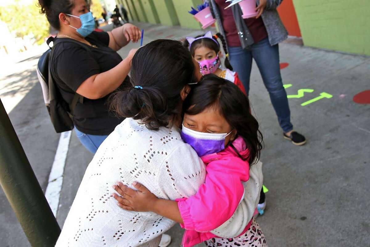 Merlin Momotiz gets a hug from her daughter Ashley Poz at Bryant Elementary School in San Francisco on April 20.