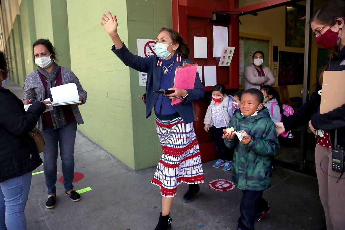 Laura Codicetti, principal of Bryant Elementary School, leads students out of school during dismissal. Bryant has two educators not returning to the classroom because of medical accommodations.