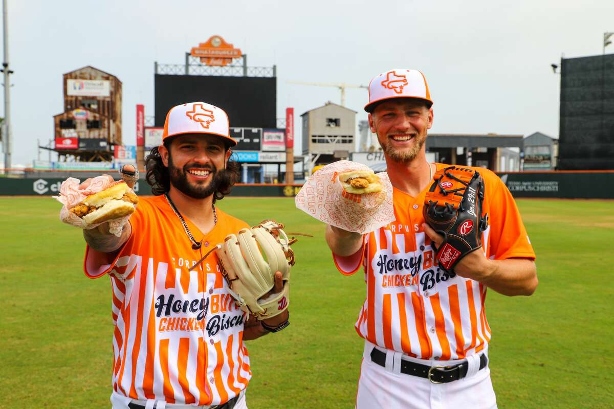 """Astros minor leaguers C.J. Hinojosa (left) and Grae Kessinger model the Corpus Christi Hooks' special """"Honey Butter Chicken Biscuits"""" uniforms that will be worn during Wednesday home games this season."""