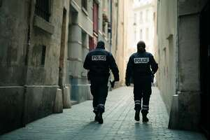 "A pair of police officers with the word ""POLICE"" written on the back of their jackets walk through a historic back alley."