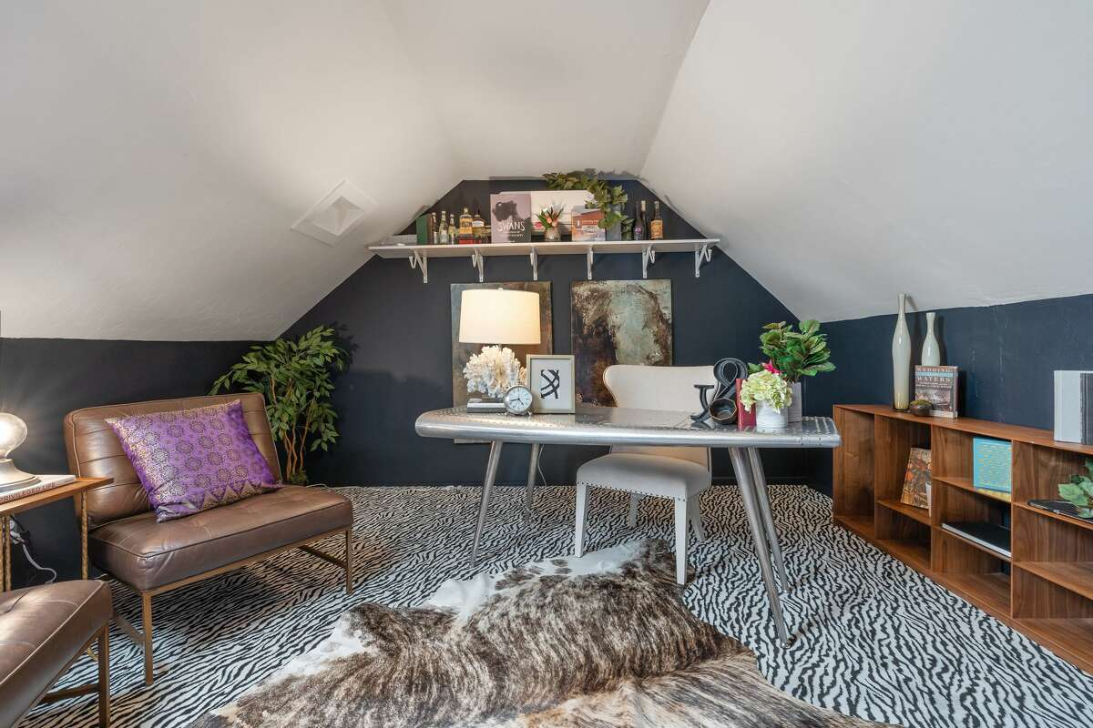 The back section of the attic has the same animal-print carpeting, but no silk ceilings to create more of an office space.