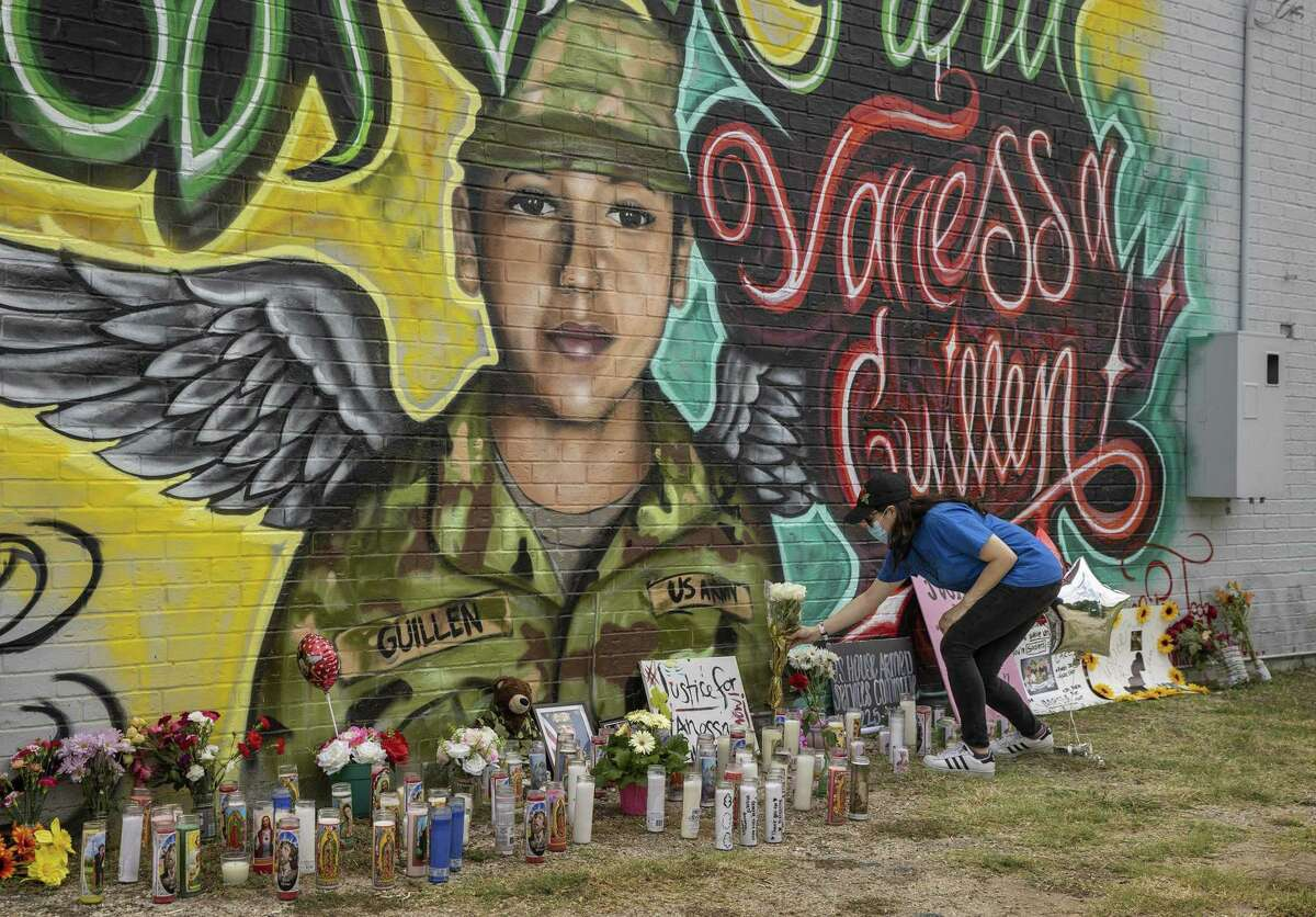 Mellisa Mendoza places white roses at a mural for Vanessa Guillen at a convenience store at East William Cannon Drive and South Pleasant Valley Road in the Dove Springs neighborhood on Monday, July 6, 2020. Guillen was a soldier the U.S. Army who went missing from Fort Hood in April, and is believed to have been killed by another soldier. (JAY JANNER/AMERICAN-STATESMAN/TNS)