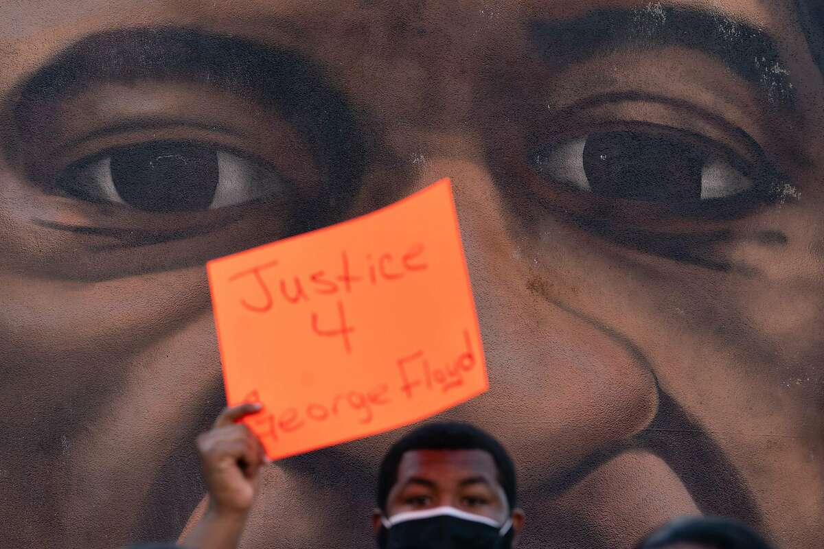 An Atlanta man holds up a sign in front of a mural of George Floyd after the guilty verdict in the trial of Derek Chauvin.