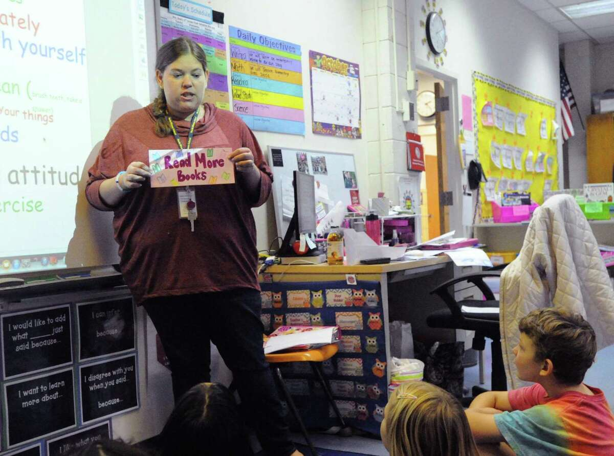 """Jennifer Dunn, a North Mianus School teacher, holds up a """"Read More Books,"""" sign, while speaking to her students at North Mianus School in Greenwich, Conn., on Thursday, Oct. 23, 2014."""