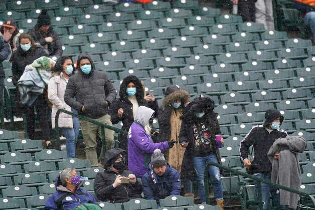 Fans in winter garb find their seat along third base in the first inning of a baseball game between the Houston Astros and Colorado Rockies on Wednesday, April 21, 2021, in Denver. (AP Photo/David Zalubowski) Photo: David Zalubowski, Associated Press / Copyright 2021 The Associated Press. All rights reserved.