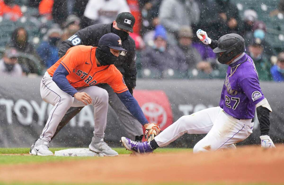 Houston Astros shortstop Carlos Correa, left, tags out Colorado Rockies' Trevor Story at third base as he tries to stretch a double into a triple in the first inning of a baseball game Wednesday, April 21, 2021, in Denver. (AP Photo/David Zalubowski)