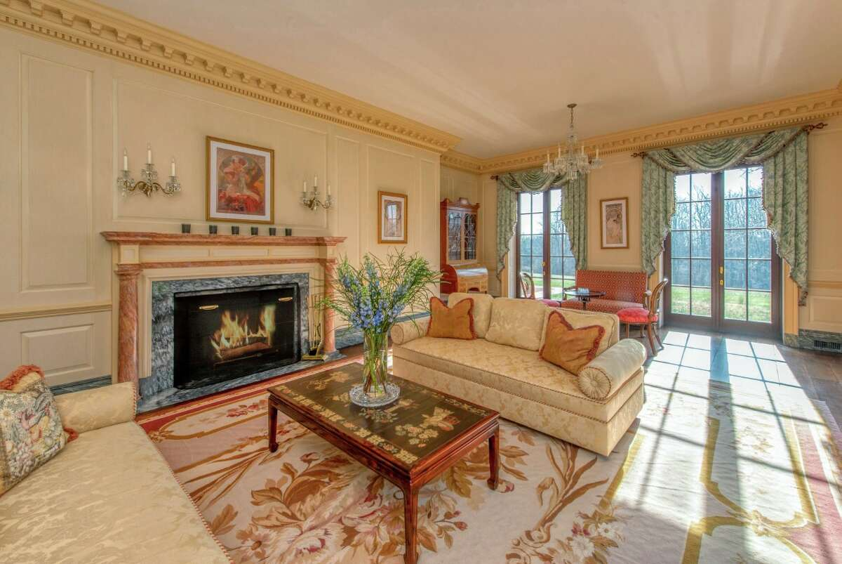 The Georgian Federal-style home at 5 1/1 Mile Road features formal living room that has French doors and a fireplace.