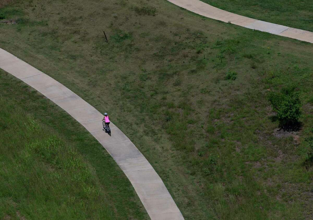 A cyclist bikes on the Brays Bayou Greenway Trail Wednesday, May 6, 2020, in Houston.