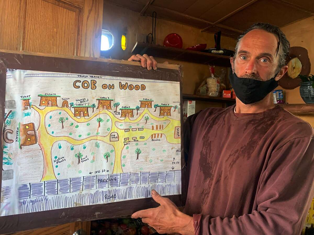 """Miguel """"Migz"""" Elliott shows his plans for Cob On Wood, a collection of earthen huts built under Interstate 880 at the Wood Street encampment in West Oakland."""