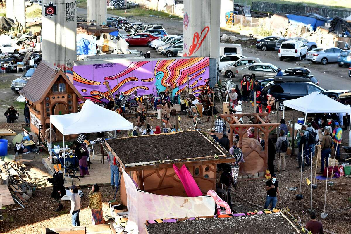 Residents and volunteers of Wood Street in West Oakland celebrate Earth Day at Cob on Wood, a new collection of earthen huts that create a community center in the homeless encampment beneath Interstate 880.