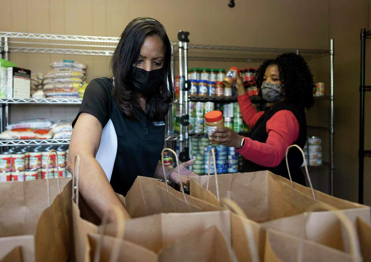 JoBess Shaw, left, loads peanut butter into bags with the assistance of Joanne Courtney at Impact Church's food pantry, Wednesday, April 21, 2021, in The Woodlands. The food pantry was opened in March to assist families and individuals facing food insecurity.