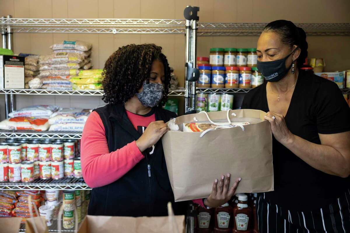 Gwendolyn Pete, right, hands Joanne Courtney a loaded bag of food at Impact Church's food pantry, Wednesday, April 21, 2021, in The Woodlands. The food pantry was opened in March to assist families and individuals facing food insecurity.