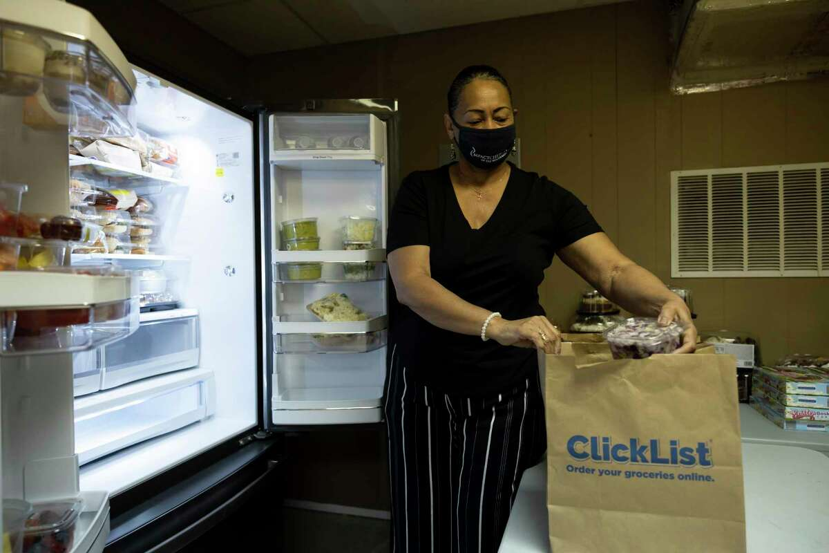 Gwendolyn Pete loads perishable items from a refrigerator into a bag at Impact Church's food pantry, Wednesday, April 21, 2021, in The Woodlands. The food pantry was opened in March to assist families and individuals facing food insecurity.