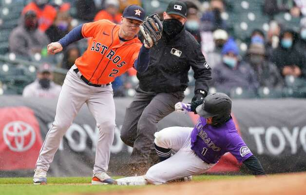 Houston Astros third baseman Alex Bregman, left, fields the throw as Colorado Rockies' Garrett Hampson steals third base in the second inning of a baseball game Wednesday, April 21, 2021, in Denver. (AP Photo/David Zalubowski) Photo: David Zalubowski, Associated Press / Copyright 2021 The Associated Press. All rights reserved.