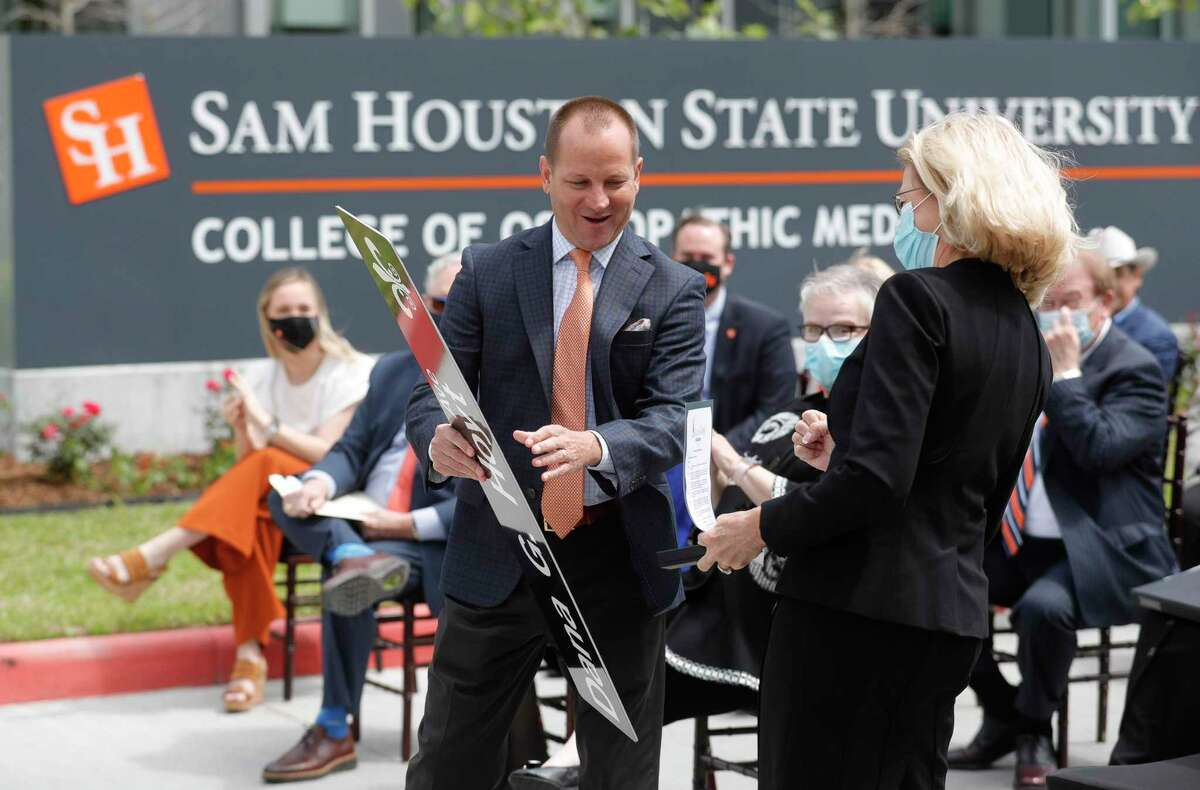 Conroe Mayor Jody Czajkoski presents Dr. Dana G. Hoyt, former president of Sam Houston State University, with a mock street sign during her street dedication ceremony at the university's College of Osteopathic Medicine, Wednesday, April 21, 2021, in Conroe.