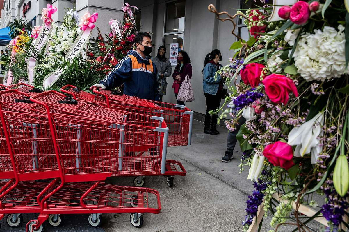 A worker prepares to provide sanitized shopping carts for customers at H Mart during its long-anticipated grand opening in the Ingleside Heights neighborhood of San Francisco.