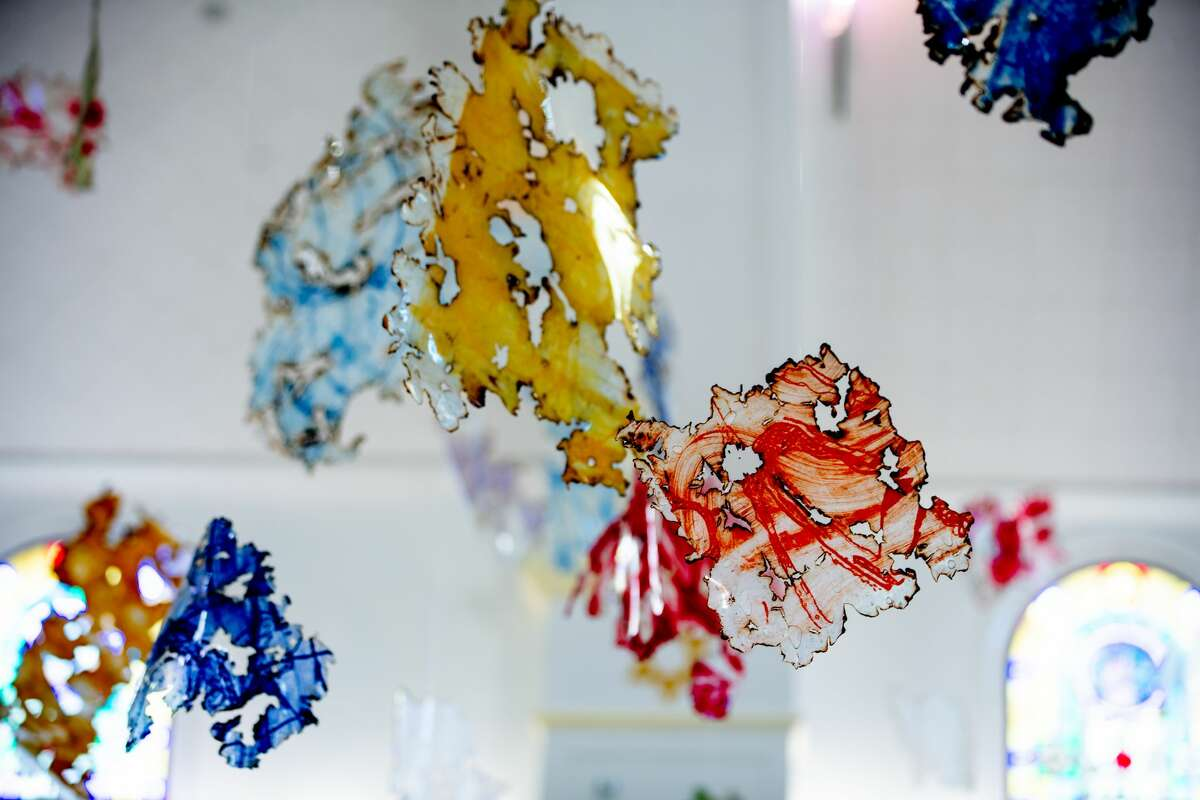 Sacred Dreams is composed of 183 strange, richly colored shapes that float near the synagogue's dome, sparkling like stained glass. But they were individually cut by hand from paper-thin sheets of jewel toned resins. Artist Mira Lehr singed the edges of each piece with a small torch to make them look as if they had been through a fierce, cosmic journey and survived, beauty intact.