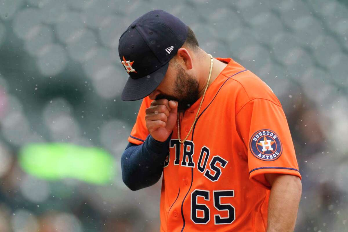 Houston Astros starting pitcher Jose Urquidy struggles to keep warm in the fifth inning of a baseball game against the Colorado Rockies Wednesday, April 21, 2021, in Denver. (AP Photo/David Zalubowski)