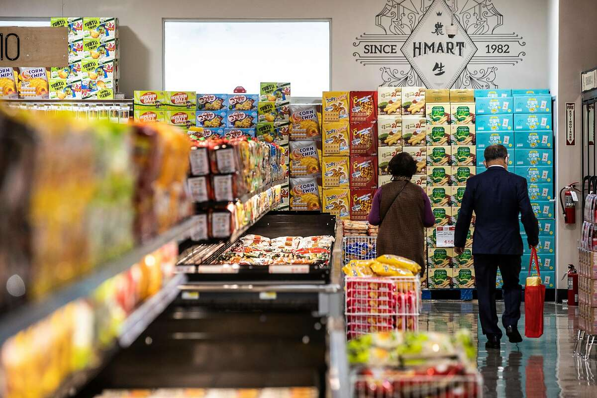 Two shoppers walk down the frozen food section at H Mart during its long-anticipated grand opening in the Ingleside Heights neighborhood of San Francisco, California Wednesday, April 21, 2021.