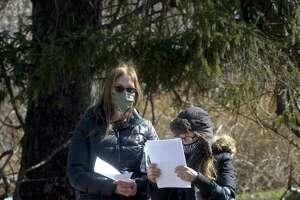 Nancy Burton, right, with friend Tracey Hansen, left, reads paperwork from the Connecticut Department of Agriculture as the department removed goats from her Redding property. The DoAg, with assistance from the Redding Police Department and the Town of Redding, executed a search and seizure warrant for goats located at 147 Cross Highway, in Redding, Conn., on Wednesday, March 10, 2021.