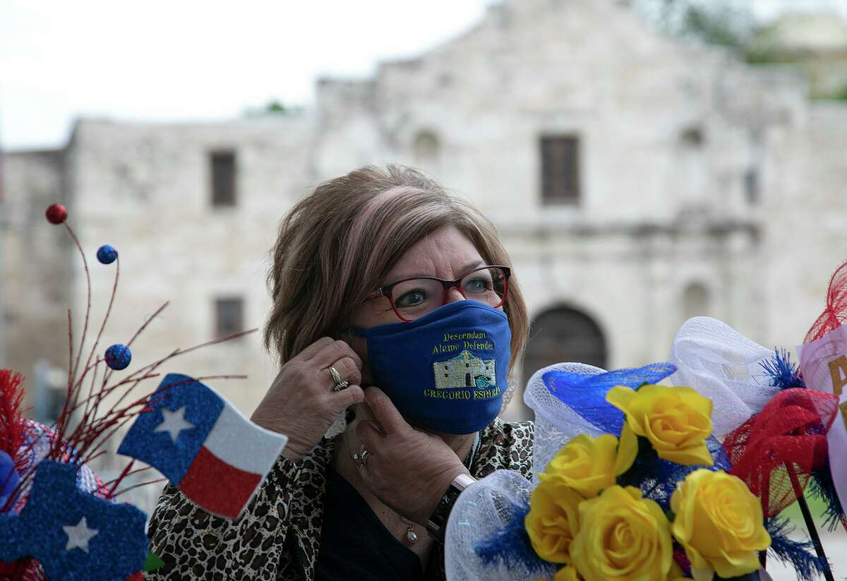 Peggy Huizar Guerrero, a direct descendant of Gregorio Esparza, adjusts her mask bearing his name before placing wreaths in front of the Alamo church in honor of the Battle of San Jacinto and fallen soldiers and volunteers at the Battle of the Alamo on April 21, 2021. The Alamo Couriers chapter and the Alamo Mission chapter of the Daughters of the Republic of Texas gathered to place the wreaths together instead of their annual pilgrimage to the Alamo.