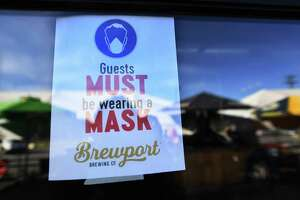 A sign informs patrons to wear masks during reopening at Brewport in Bridgeport May 19, 2020.