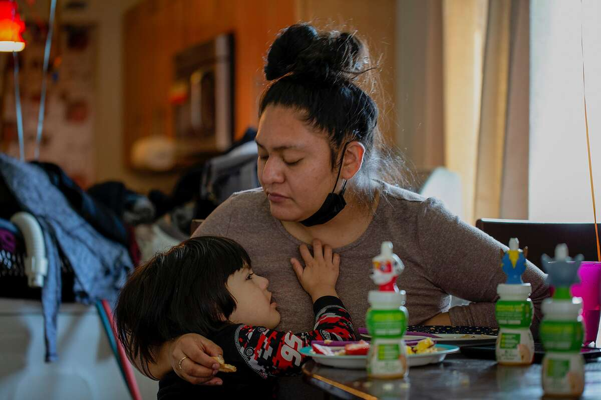 Aracely Nava, with her son Fares Arriaga, said she was afraid of virus contagion while she worked at a San Francisco fast-food restaurant during the pandemic.