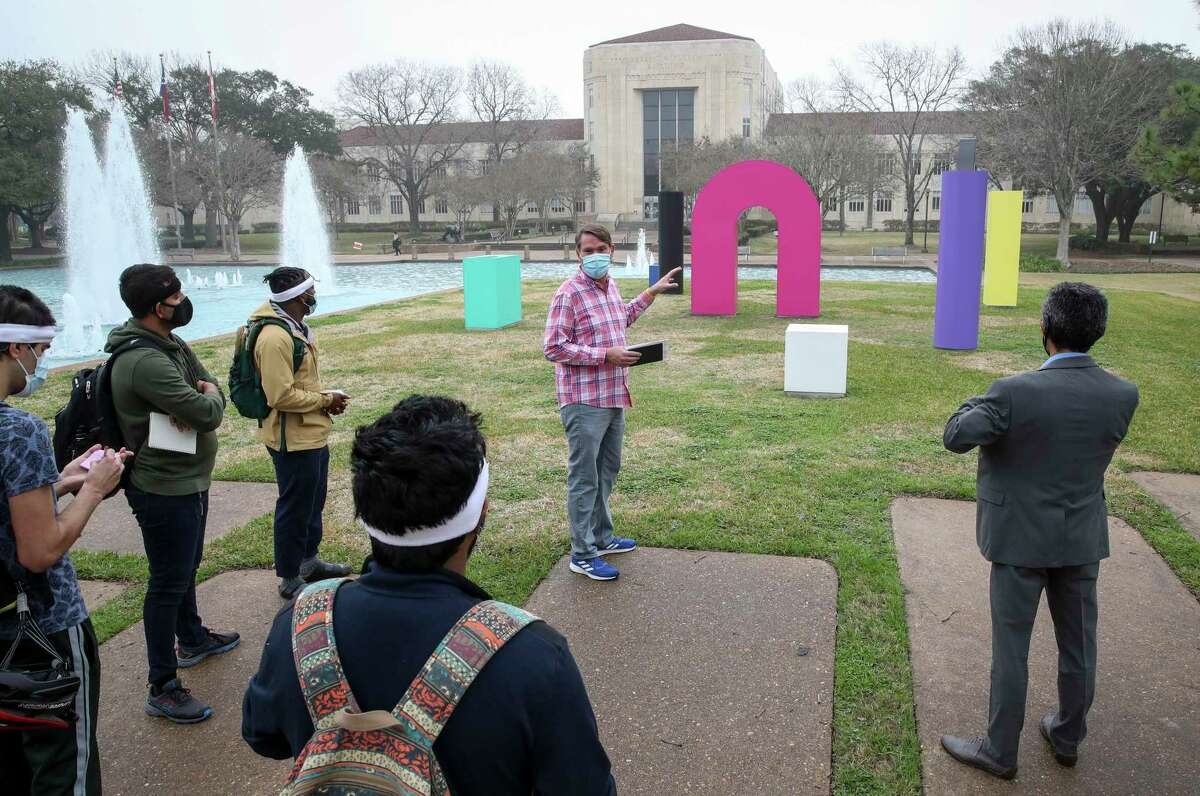 """Mike Guidry, center, curator of public art at the University of Houston, tells students about """"Forms of Life,"""" a piece by the artist TYPOE, as they take part in a walking tour of the """"Color Field"""" outdoor art exhibition while wearing mobile brain-body imaging headsets Tuesday, Feb. 9, 2021, in Houston."""