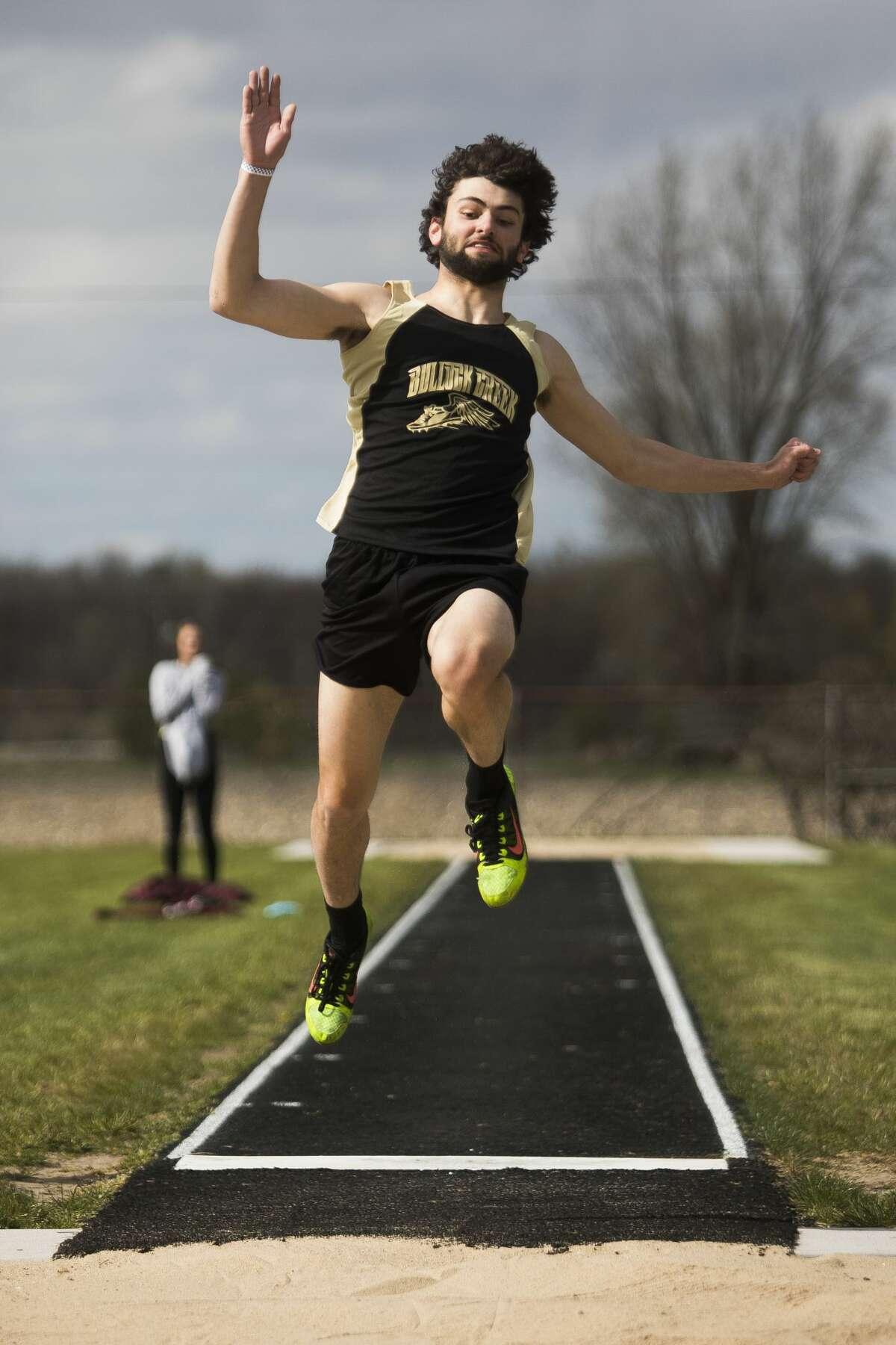 Bullock Creek's Brandon Fowler competes in the long jump event during a track meet Wednesday, April 21, 2021 at Bullock Creek High School. (Katy Kildee/kkildee@mdn.net)