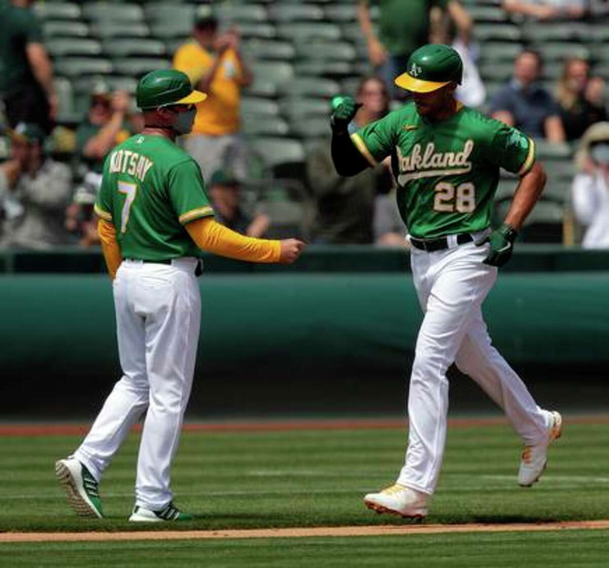 Matt Olson (28) high fives third base coach Mark Kotsay as he rounds the bases on his solo homerun in the second inning as the Oakland Athletics played the Minnesota Twins at the Oakland Coliseum in Oakland, Calif., on Wednesday, April 21, 2021.