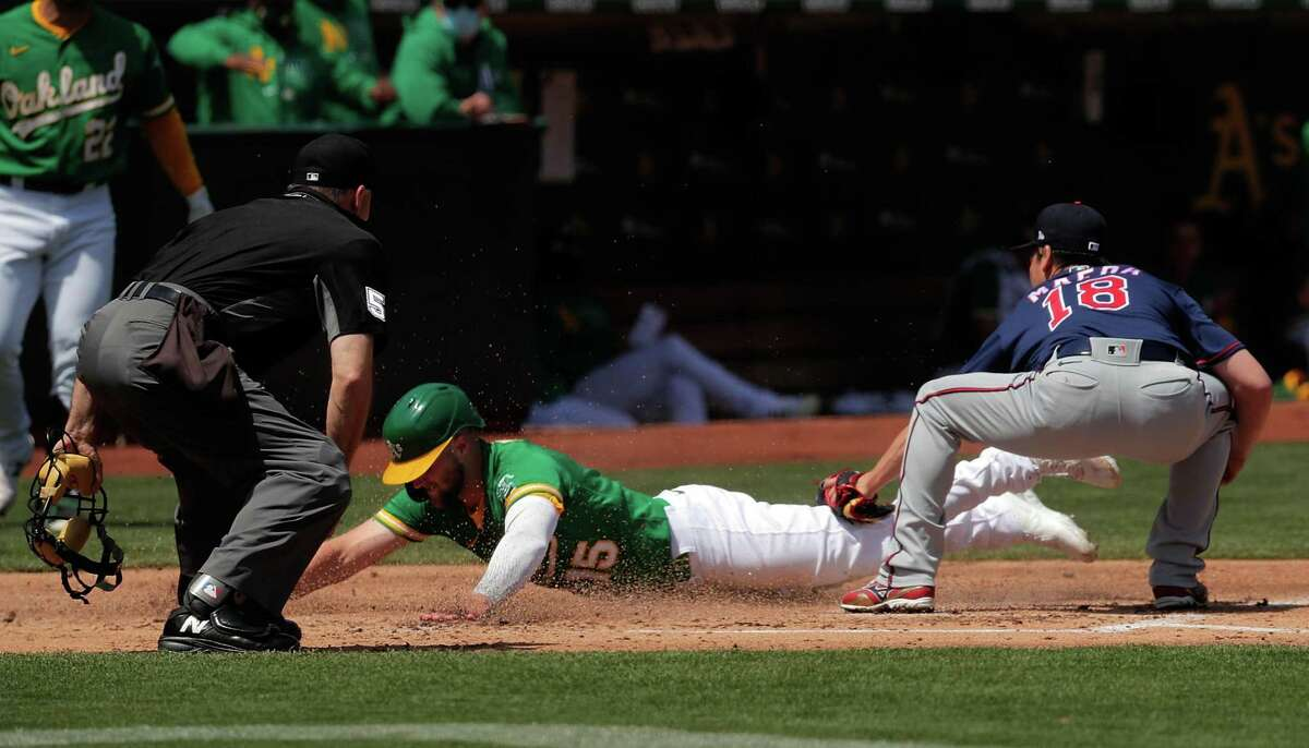 Seth Brown (15) scored on a wild pitch past Kenta Maeda (18) on a wild pitch in the second inning as the Oakland Athletics played the Minnesota Twins at the Oakland Coliseum in Oakland, Calif., on Wednesday, April 21, 2021.