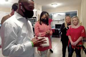 """From left, Reverend Kennedy Andrews offers up a house blessing as wife Deanna, Rhonda Smith and her daughter, house founder, Brandi Hammond, stand by during a """"Links and Drinks"""" fundraiser to kick off the opening of Hammond House, a sober living home for women and children in Beaumont. Photo made Saturday, April 3, 2021 Kim Brent/The Enterprise"""