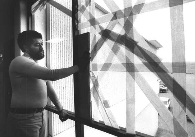James W. Beard Jr., associate dean of the TSU Thurgood Marshall School of Law, shows the mass of crisscrossed tape that holds together one of 11 broken windows in the building in this Dec. 30, 1979, file photo. The building, less than four years old, has many physical disabilities, according to Beard and other school officials. They blamed the building's rundown condition on a lack of maintenance. Photo: Buster Dean, Staff File Photo/Houston Chronicle