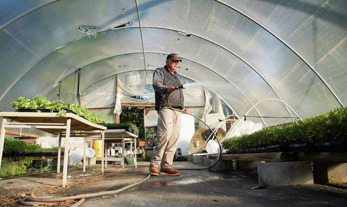 Van Weldon, owner of Wood Duck Farm, waters future transplants in his greenhouse in Cleveland on Wednesday, April 21, 2021.
