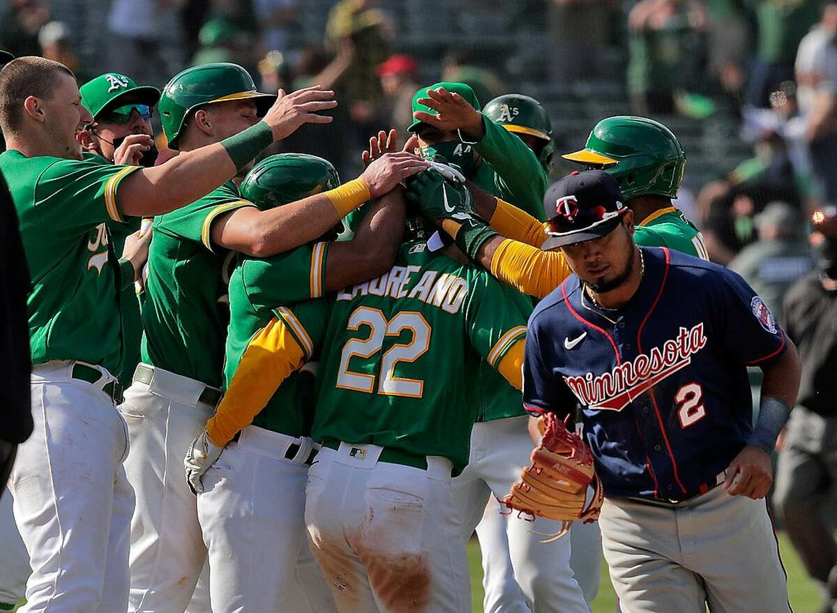 The A's mob Ramon Laureano (22) as Twins third baseman Luis Arraez (2) runs by after he reached on a throwing error by Arraez scoring two runs as the Oakland Athletics defeated the Minnesota Twins 13-12 in 10 innings at the Oakland Coliseum in Oakland, Calif., on Wednesday, April 21, 2021.