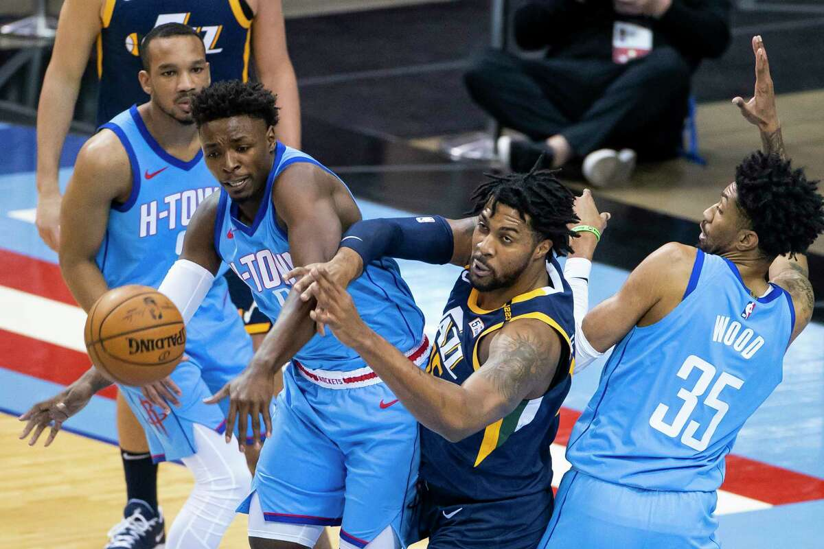 Houston Rockets forward Jae'Sean Tate (8) and Houston Rockets center Christian Wood (35) knock the ball away from Utah Jazz center Derrick Favors (15) during the first quarter of an NBA game between the Houston Rockets and Utah Jazz on Wednesday, April 21, 2021, at Toyota Center in Houston.