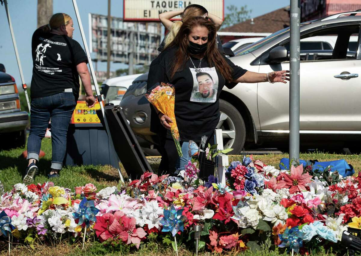 Leantha Chavez, center, places a bouquet of flowers at the memorial site for her son, Nicolas Chaves, on the intersection of Gazin Street and East Freeway Service Road on Wednesday, April 21, 2021, in Houston. Chavez's family is marking one year since his death by holding a cookout on the intersection where he was fatally shot by Houston Police.
