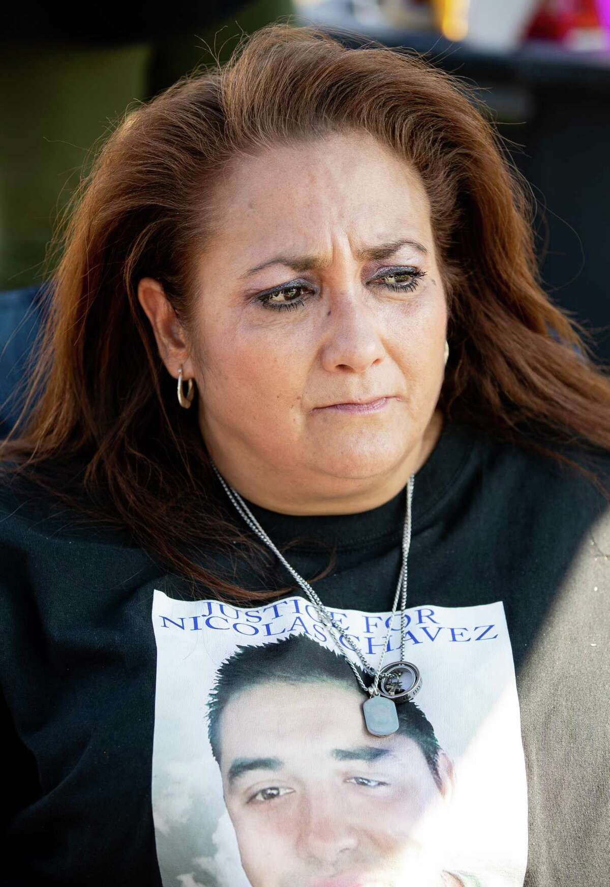 Leantha Chavez, center, wears a necklace with the picture of her son, Nicolas Chavez, on Wednesday, April 21, 2021, in Houston. Chavez's family is marking one year since his death by holding a cookout on the intersection where he was fatally shot by Houston Police.