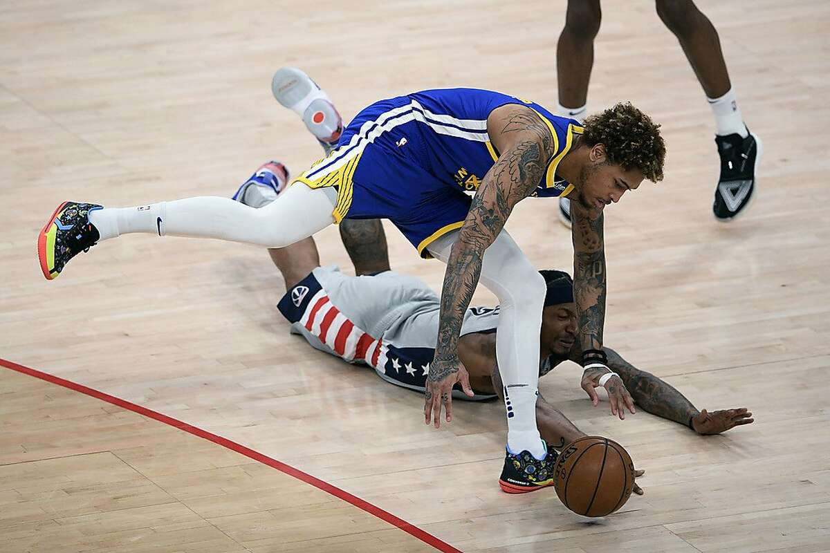 Golden State Warriors guard Kelly Oubre Jr., top, and Washington Wizards guard Bradley Beal, bottom, battle for the ball during the first half of an NBA basketball game, Wednesday, April 21, 2021, in Washington. (AP Photo/Nick Wass)