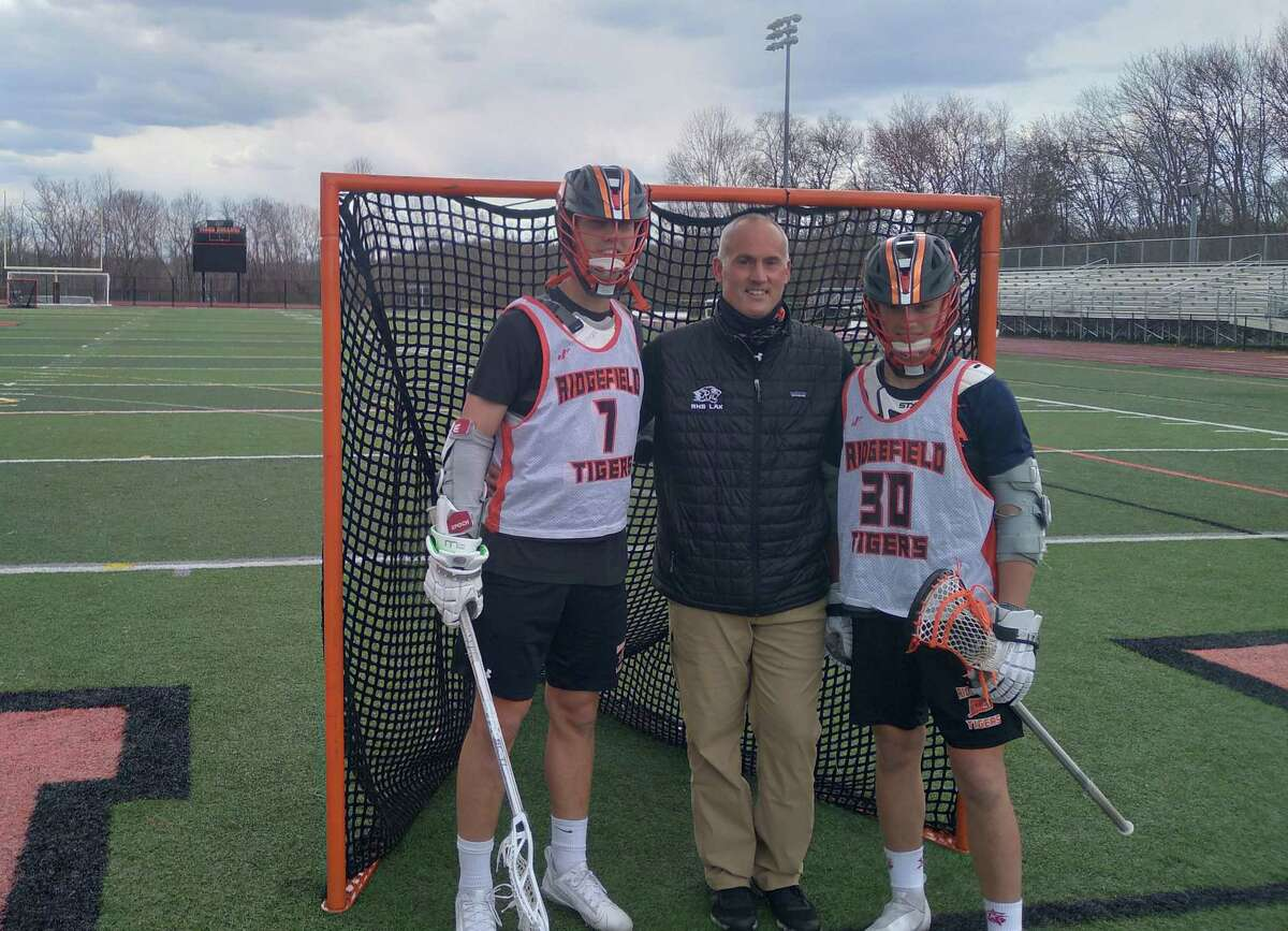 Junior Ryan Colsey, left, and freshman Kyle Colsey, right, flank their father and their coach at Ridgefield boys lacrosse, Roy Colsey, at Tiger Hollow in Ridgefield, Conn. Ryan and Kyle are attackmen for the Tigers.
