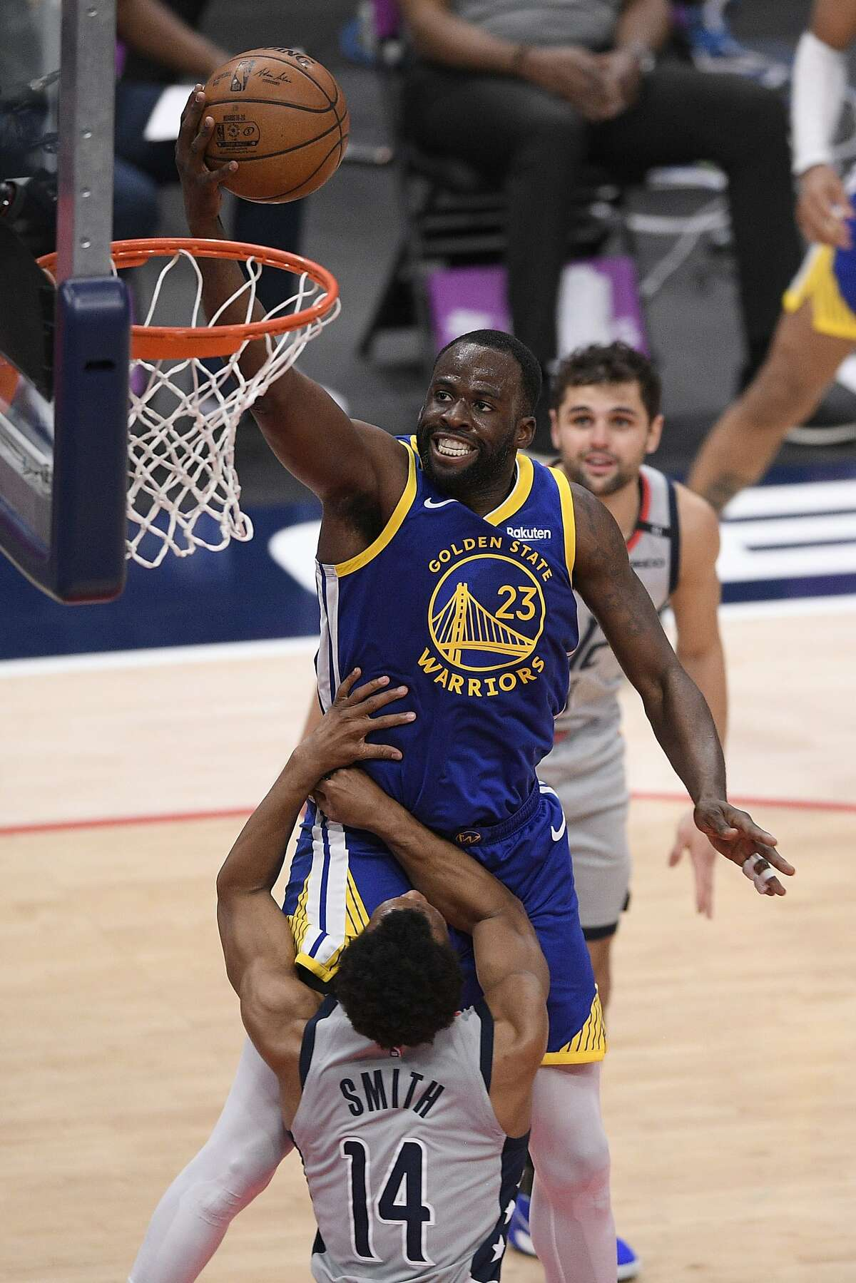 Golden State Warriors forward Draymond Green (23) goes to the basket against Washington Wizards guard Ish Smith (14) during the second half of an NBA basketball game, Wednesday, April 21, 2021, in Washington. (AP Photo/Nick Wass)
