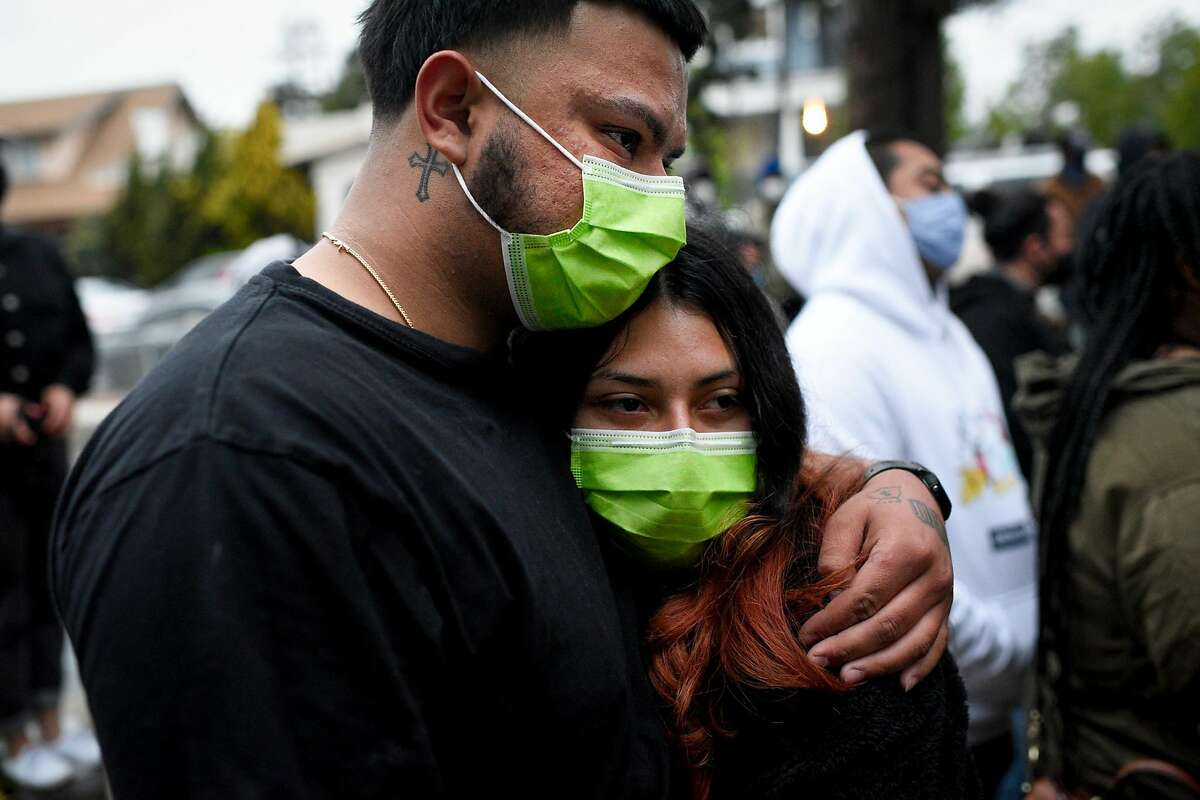 Jose Gonzalez hugs Goyaa Barrera, both of Oakland, during an April 21 press conference regarding the death of Gonzalez's friend Mario Gonzalez in Alameda police custody.