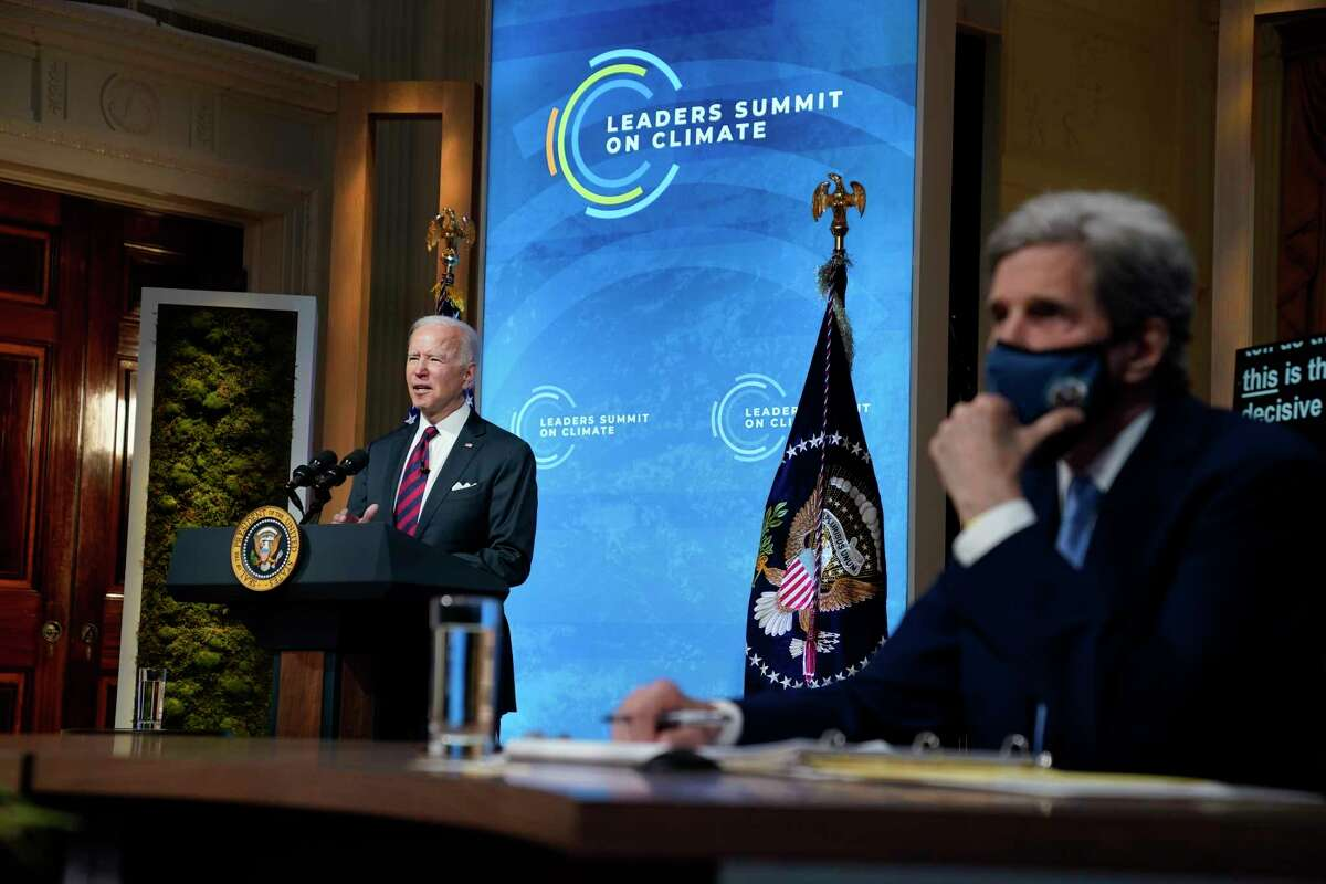 President Joe Biden speaks to the virtual Leaders Summit on Climate, from the East Room of the White House, Thursday, April 22, 2021, in Washington, as Special Presidential Envoy for Climate John Kerry, looks on.