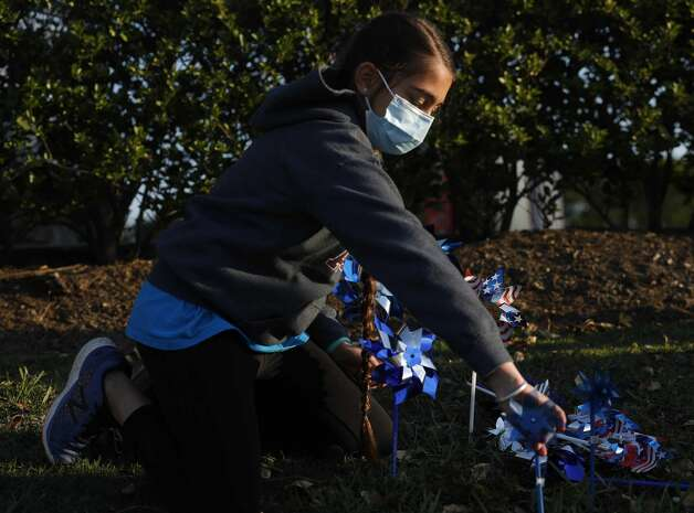 Amiya Casperson helps install pinwheels as volunteers and community members place 2,322 pinwheels along FM 1488 and FM 2978, Thursday, April 22, 2021, in Magnolia. The annual installation by Children's Safe Harbor recognizes the number of child cases in Montgomery County and raises awareness of Child Abuse Prevention and Awareness Month. Photo: Jason Fochtman/Staff Photographer / 2021 ? Houston Chronicle