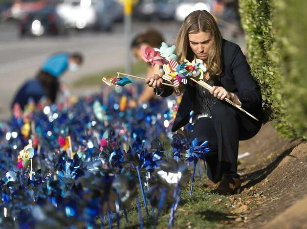 Montgomery County Assistant District Attorney Shanna Redwine helps install pinwheels as volunteers and community members place 2,322 pinwheels along FM 1488 and FM 2978, Thursday, April 22, 2021, in Magnolia. The annual installation by Children's Safe Harbor recognizes the number of child cases in Montgomery County and raises awareness of Child Abuse Prevention and Awareness Month.  Photo: Jason Fochtman/Staff Photographer / 2021 ? Houston Chronicle