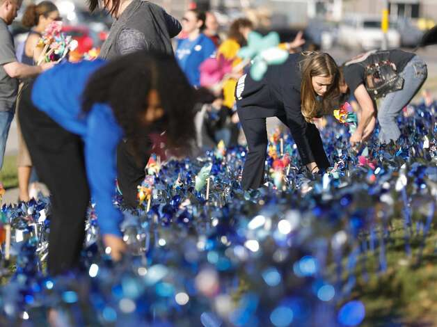 Montgomery County Assistant District Attorney Shanna Redwine, second from left, helps install pinwheels as volunteers and community members place 2,322 pinwheels along FM 1488 and FM 2978, Thursday, April 22, 2021, in Magnolia. The annual installation by Children's Safe Harbor recognizes the number of child cases in Montgomery County and raises awareness of Child Abuse Prevention and Awareness Month.  Photo: Jason Fochtman/Staff Photographer / 2021 ? Houston Chronicle