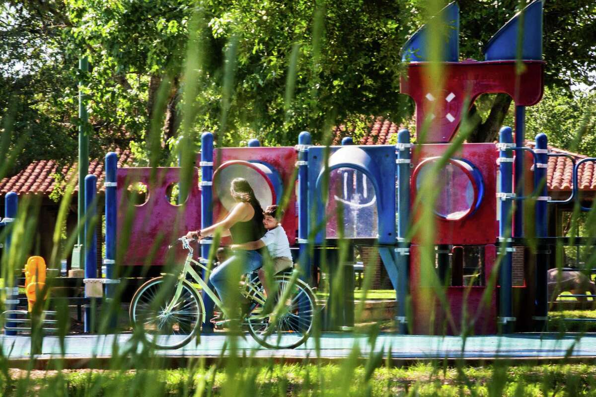 View of a child and a woman on a bicycle through Cereal Rye at Hermann Park, Tuesday, April 20, 2021, in Houston. Cereal Rye has been planted as part of efforts to nourish the underground ecosystems of the park's soil.