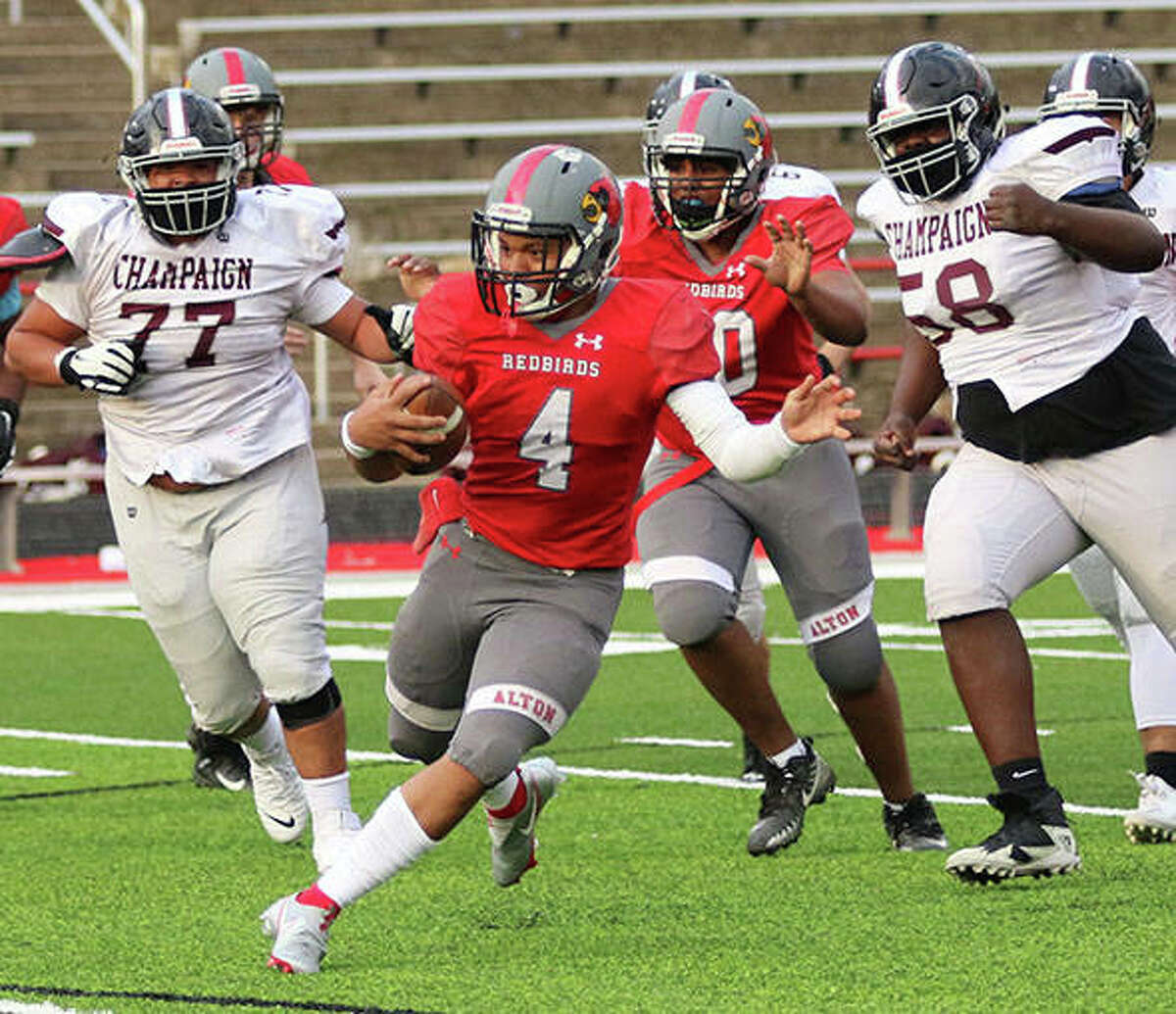 Alton quarterback Keith Gilchrese (4) heads upfield with Champaign Central linemen in pursuit during a March 30 game at Public School Stadium in Alton. The Redbirds finish their season Friday night at Belleville West.